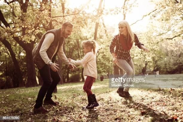 Cheerful parents with their little daughter playing in park.