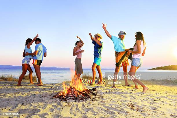 Cheerful people dancing next to the campfire.