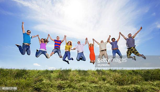 Cheerful people holding hands and jumping high up against sky.