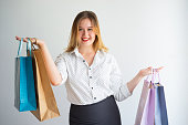 Cheerful playful woman weighing shopping bags and looking at camera. Jolly confident girl choosing goods for purchase. Shopping for body positive concept