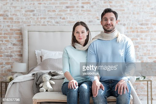Cheerful positive couple sitting next to each other : Foto de stock