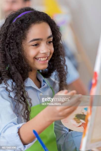 Cheerful preteen girl in art class