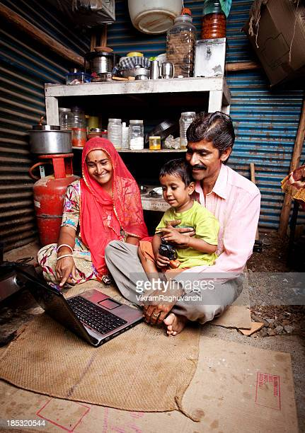 Cheerful Rajasthani Rural Indian Mother Father and Son Using Laptop