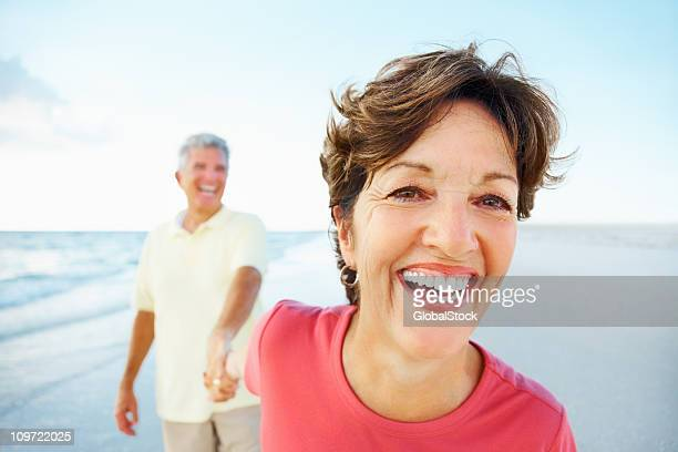 Cheerful retired couple having a good time on beach