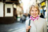 Closeup of positive retiree woman having a walk in city
