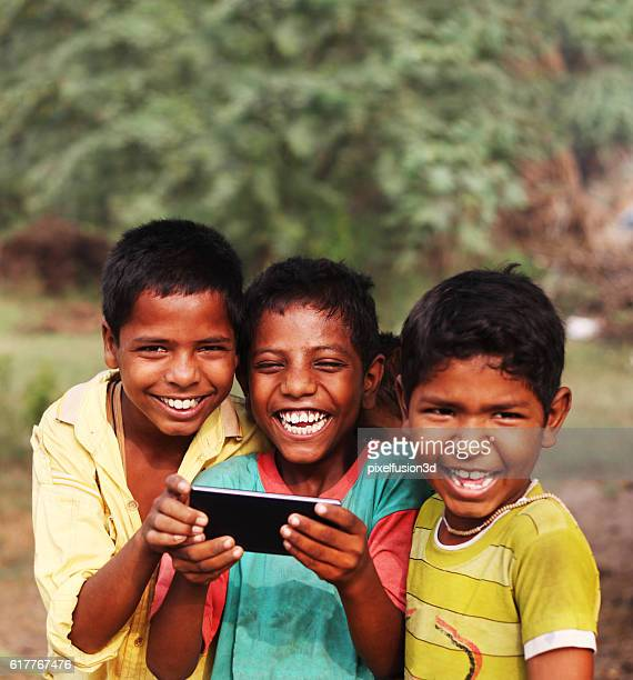 Cheerful rural children holding Smartphone