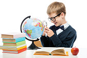 cheerful schoolboy with a magnifying glass examines the globe at the table, portrait is isolated