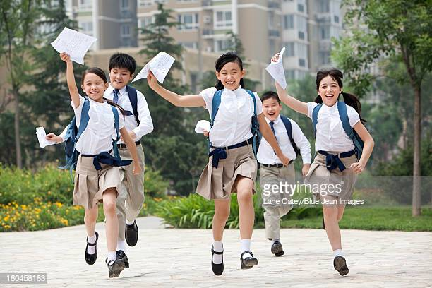 Cheerful schoolchildren in uniform with results lists in hands