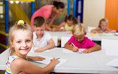 Cheerful schoolgirl in elementary school class indoors