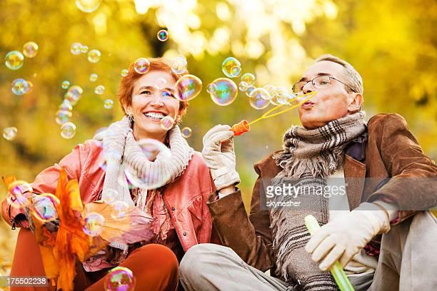 Joyeux couple senior envoyer des bulles dans le parc