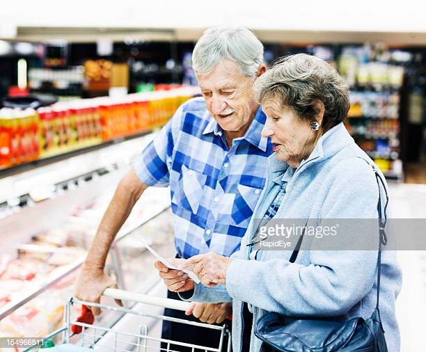 Cheerful senior couple check their shopping list in supermarket