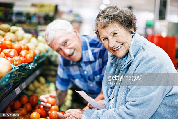 Cheerful senior couple choose vegetables in the supermarket