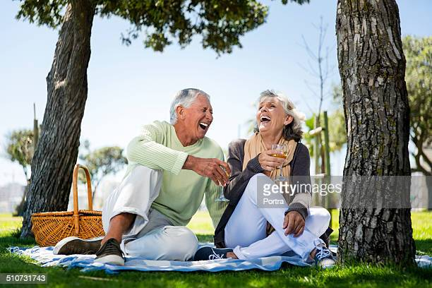 Cheerful senior couple having wine at park