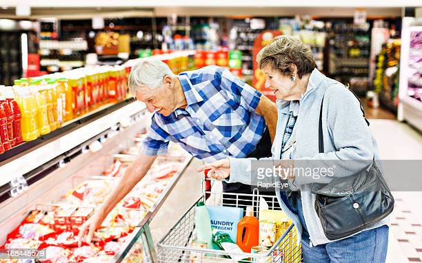 Cheerful senior couple make selection from supermarket fridge