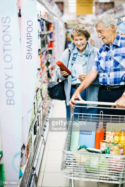 Cheerful senior couple shop for toiletries in supermarket