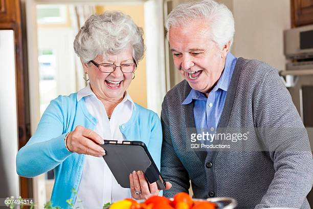 Cheerful senior couple video chat with family while preparing dinner