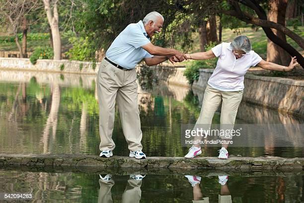 Cheerful senior man and woman having fun at park