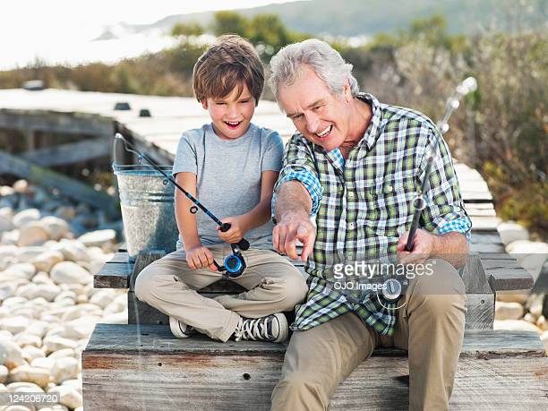 Cheerful senior man fishing with boy on pier