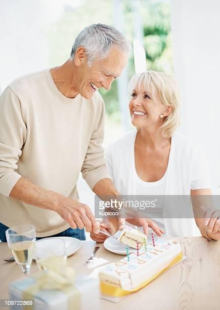 Cheerful senior man giving slice of cake to mature woman