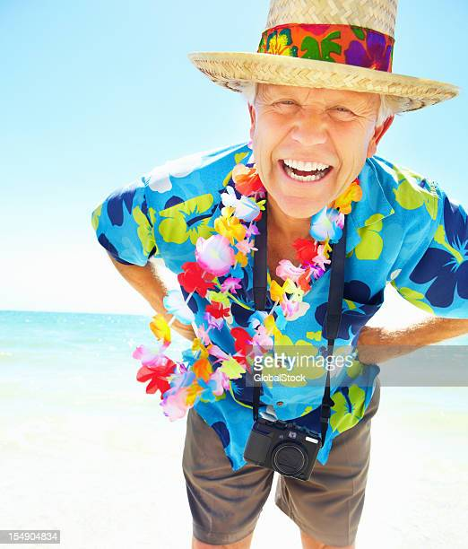 Cheerful senior man on vacation posing with hands on hips