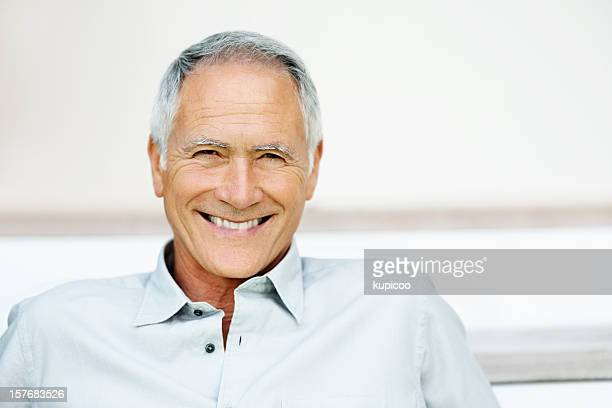 Cheerful senior man smiling against colored background