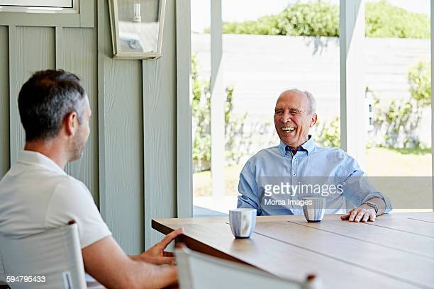 Cheerful senior man with son on patio