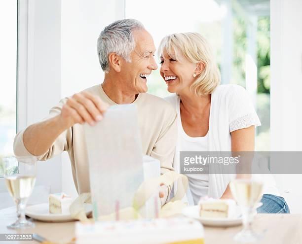 Allegro uomo anziano con donna aprendo il regalo di compleanno