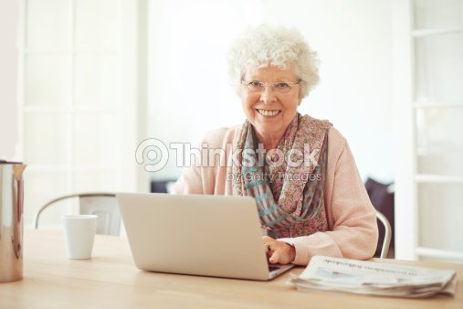 joyeuse femme senior la maison avec ordinateur portable photo thinkstock. Black Bedroom Furniture Sets. Home Design Ideas