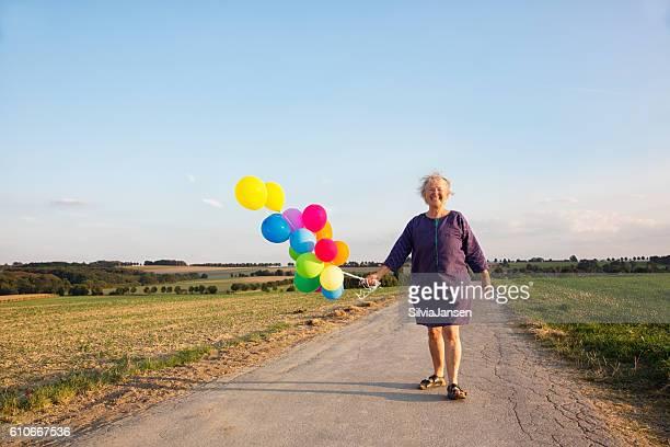 cheerful  senior woman holding balloons in rural scene