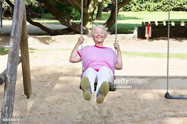 cheerful  senior woman on playground using a swing