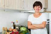 cheerful senior woman standing against kitchen interior background