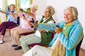 Group of four smiling senior women toning their arms with elastic strengthening bands while seated in fitness class.