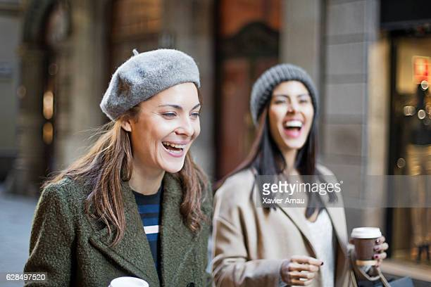 Cheerful shopaholic female friends on city street