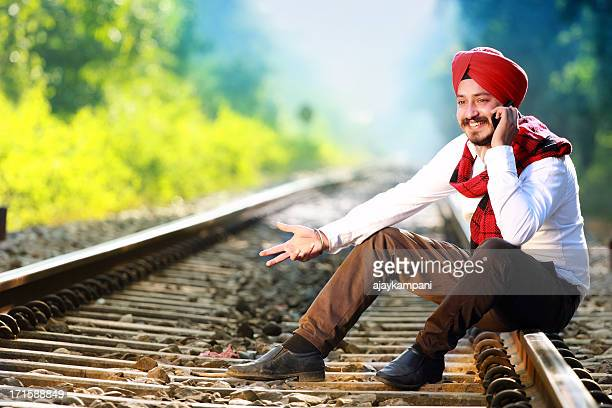 Cheerful Sikh man talking on a mobile phone