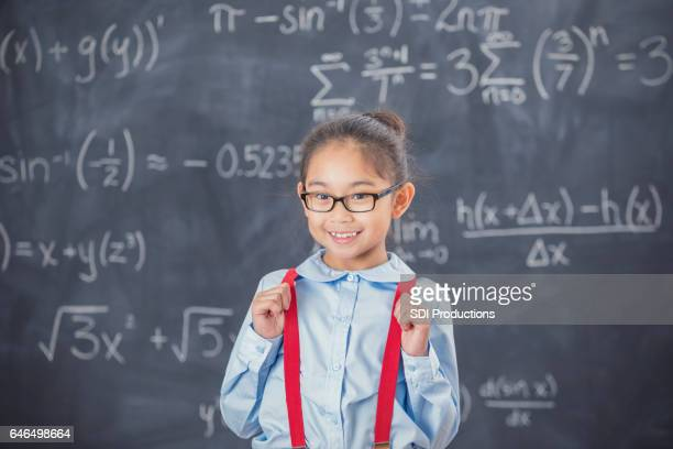 Cheerful smart elementary schoolgirl in front of chalkboard