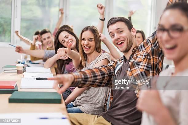 Alegre estudiantes celebrando en montaje tipo aula y mirando a la cámara