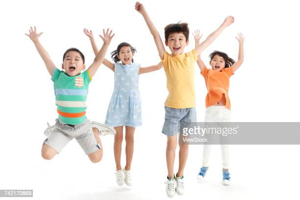 Cheerful students jumping with arms raised