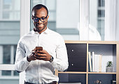 Chatting with pleasure. Portrait of happy young qualified african man in glasses is standing in light office and holding mobile phone. He is reading messages on gadget with smile. Copy space