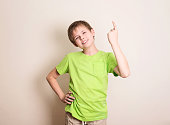 Cheerful teen boy pointing up over white wall.