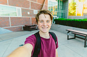 Teen student boy with blue eyes and brown hair wearing a backpack selfie with teeth smile