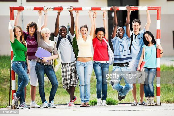 Cheerful teenage friends standing at the playground.