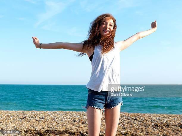 A cheerful teenage girl standing on the beach with her arms raised in exhilaration
