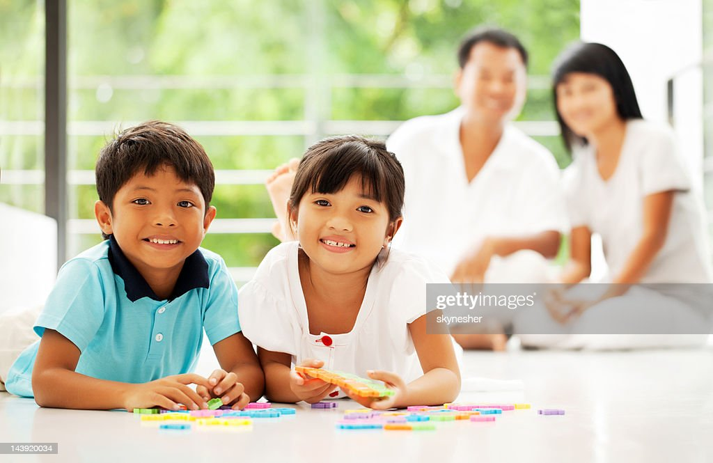 Cheerful Thai children playing with puzzle at home. : Stock Photo