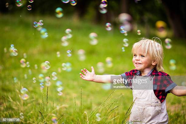 Bébé joyeux garçon jouant avec des bulles de savon dans le parc