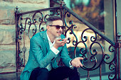 Handsome stylish man in elegant suit and sunglasses leaving message using voice recognition, speaking at smartphone on street.
