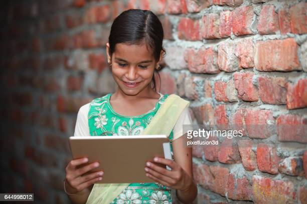 Cheerful village girl watching in tablet