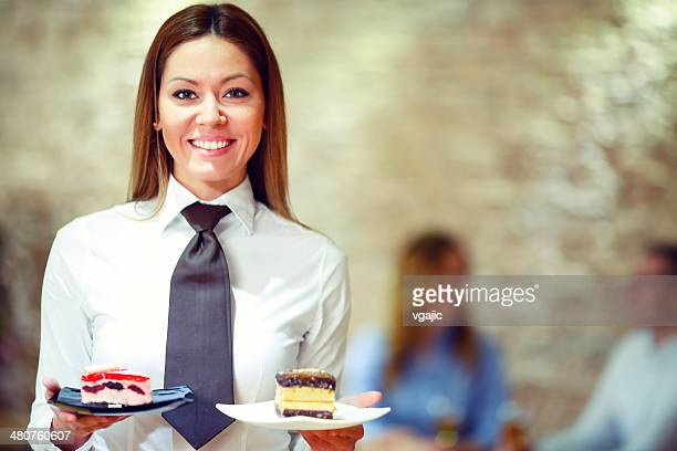 Cheerful waitress with desserts.