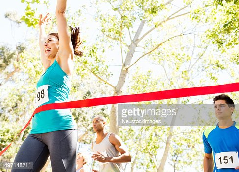 Cheerful Woman Crossing Finish Line Of Marathon