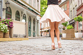 Cheerful woman in nude high hell shoes dancing on the street