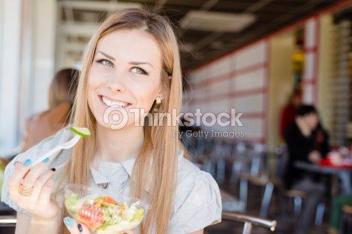 Alegre mujer comiendo ensalada en el cafe : Foto de stock